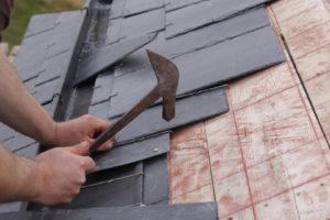 Ouvrier couvreur en train de faire une toiture